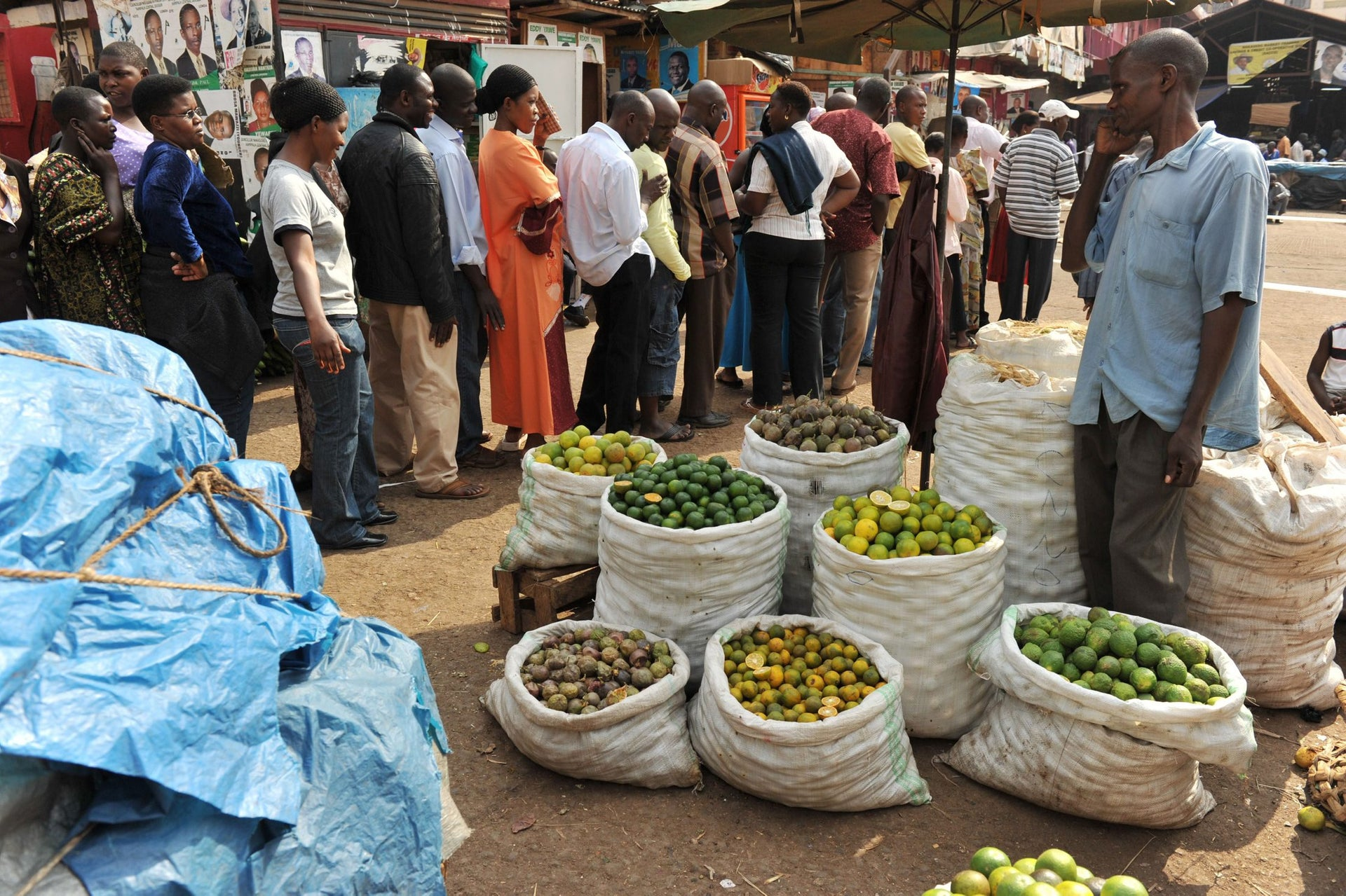 A fruit vendor at a market looks at voters waiting in line at a polling station in Uganda's capital Kampala on February 18, 2011 to vote in presidential and parliamentary elections.