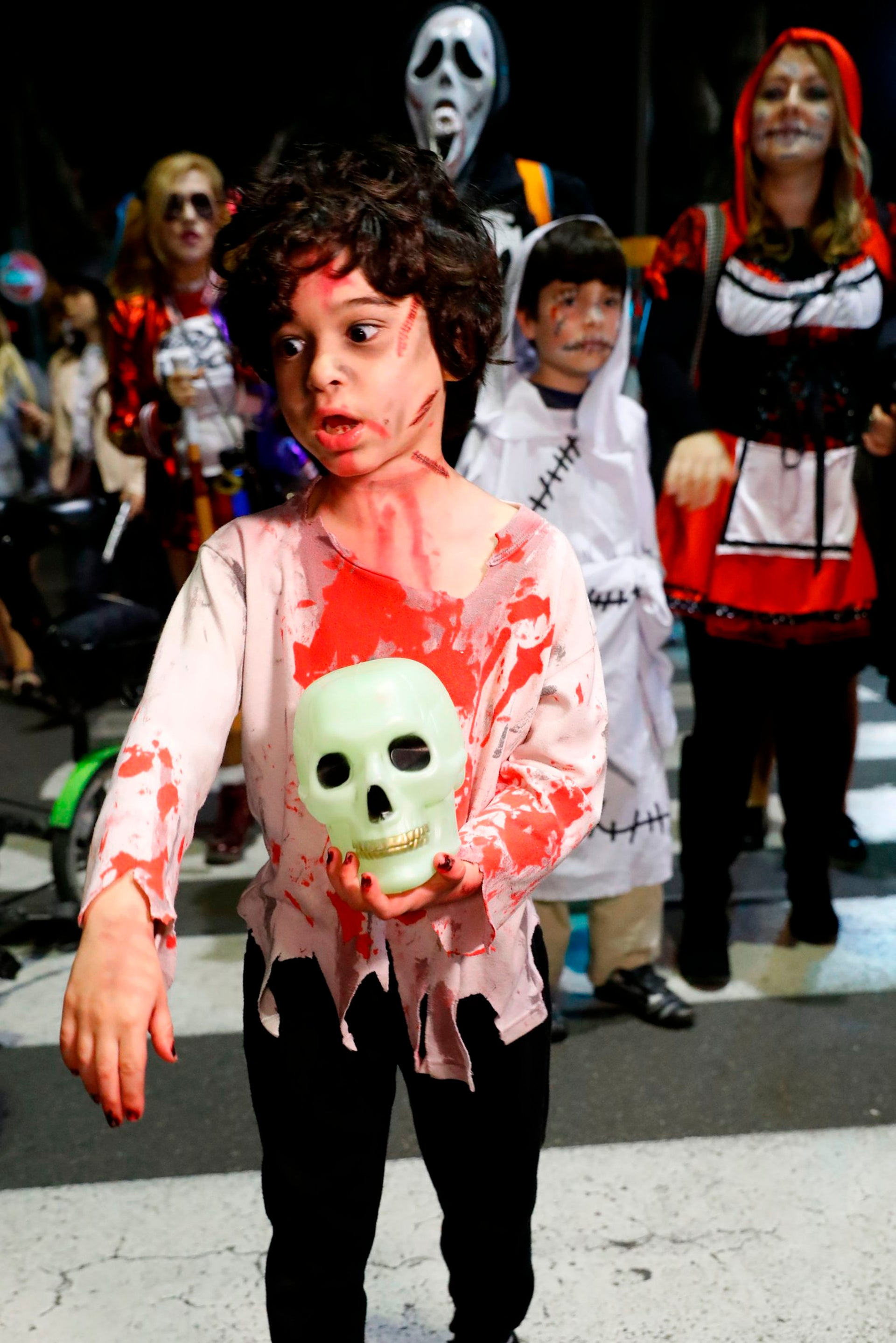 "A woman boy costumes and face paint takes part in a ""Zombie walk"" in Tel Aviv as part of the Jewish holiday of Purim on March 3, 2018."
