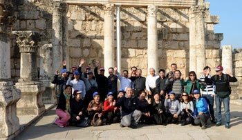 Chinese tourists standing in front of the remains of an ancient synagogue at the archaeological site in Capernaum.