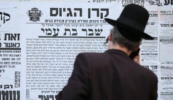 An ultra-Orthodox man walks past advertisements against drafting Haredim to the army, Mea Shearim, Jerusalem, March 4, 2018.