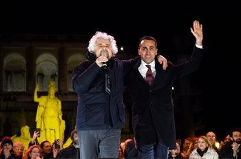 Italy's populist 5 Star Movement founder Beppe Grillo addresses supporters with party's leader Luigi di Maio (R) during the last election campaign meeting in Rome's Piazza del Popolo. March 2, 2018