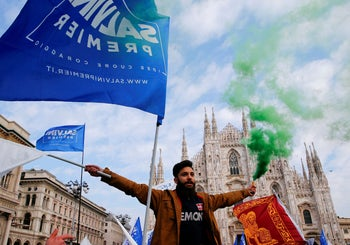 A supporter of the Italian far-right Northern League holds a flare during a political rally led by leader Matteo Salvini in Milan, Italy. February 24, 2018