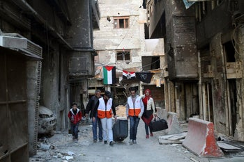 Members of the Syrian Red Crescent help people leave the Palestinian Yarmouk refugee camp where loyalists of President Bashar Assad have steadily intensified a blockade to prevent food and aid from entering over the past year, on the southern edge of Damascus, Syria, Saturday, Feb. 1, 2014.