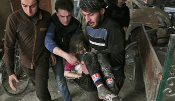 Syrians carry a wounded child following reported government bombardments on the rebel-held town of Hamouria, in the besieged eastern Ghouta, March 5, 2018.