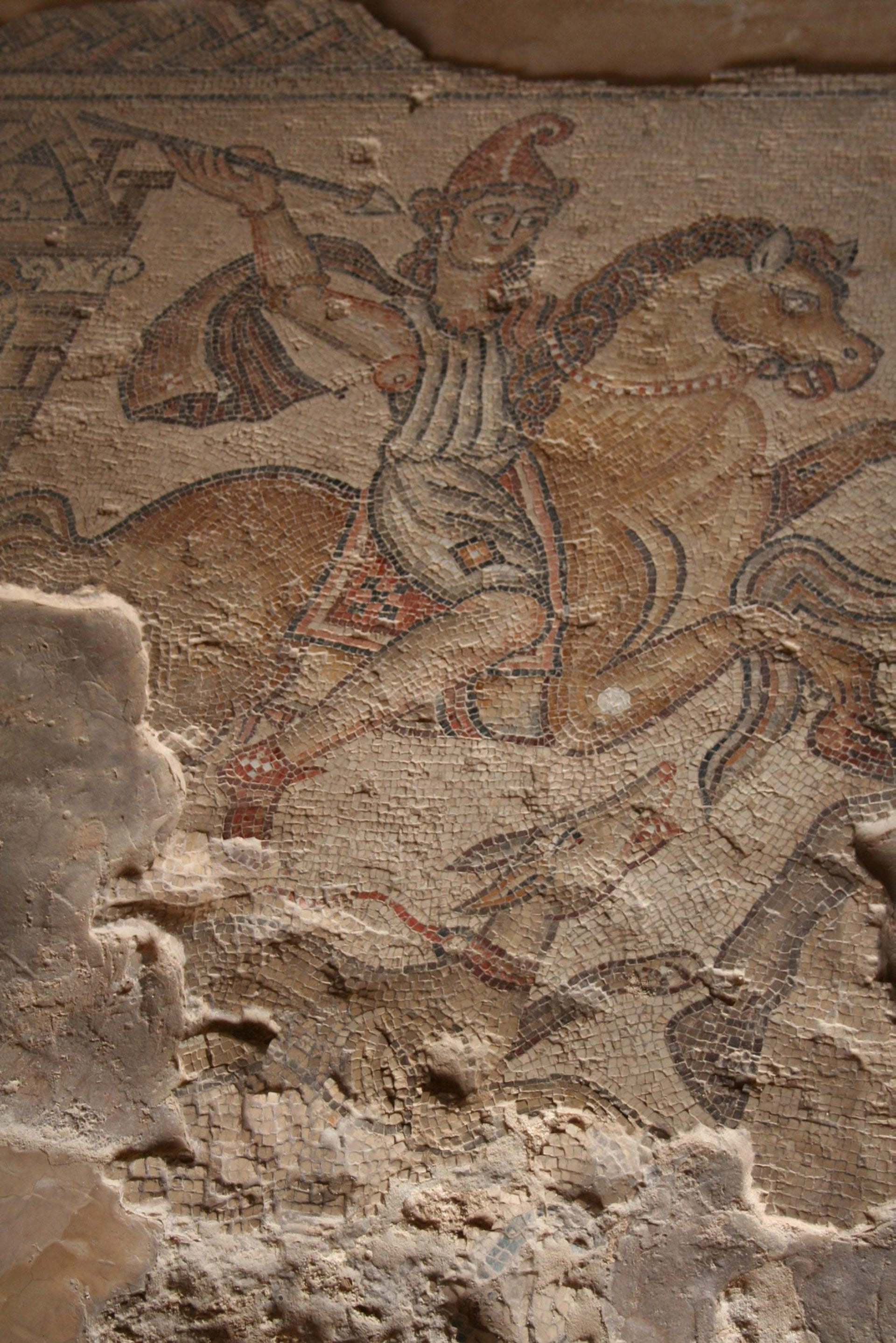 Among the amazing mosaics at Zippori: Photo shows mosaic mage of helmeted warrior on a rearing horse, wearing a toga-type garb and brandishing a spear. Beneath the front leg of the quadruped there seems to be a hunting dog with an elongated snout.