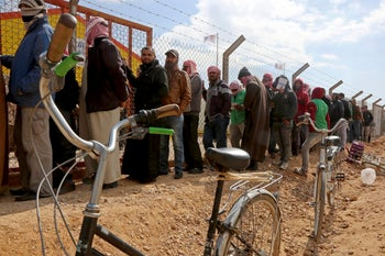 Syrian refugees line up to register at an employment office at the Azraq Refugee Camp in Jordan, February 18, 2018.