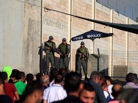 FILE PHOTO: Israeli border police officers stand guard as Palestinians wait to cross through the Qalandia checkpoint to attend Ramadan prayer in Jerusalem's al-Aqsa mosque, near Ramallah June 10, 2016.