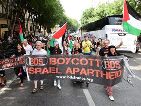 FILE PHOTO: Protesters march behind a banner of the BDS organization in France, June 13, 2015.
