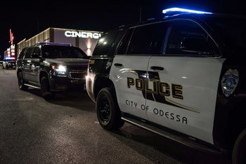 Police cars and tape block off a crime scene where a gunman was shot and killed at Cinergy Odessa movie theater, Midland, Texas, August 31, 2019.