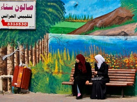 Two Israeli Arab women wait for transportation in front of a wall mural and a sign in Arabic reading 'Sana's bridal shop' in the northern Israeli Arab town of Umm Al-Fahm. April 23, 2009