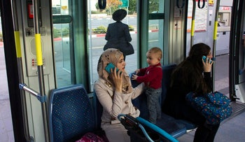 Women speak on their phones as they ride a light rail tram in Jerusalem November 11, 2014