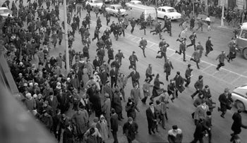 FILE PHOTO: A black and white photo showing people running away as police attack near the Warsaw University during the 1968 student riots in Poland.