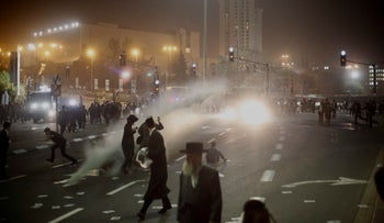 Israeli police uses water cannons as ultra-Orthodox Jews block the entrance to Jerusalem during a military draft protest. March 8, 2018.