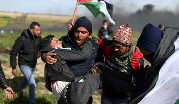 A wounded Palestinian is evacuated during clashes with Israeli troops at a protest against Trump's decision on Jerusalem, near the border with Israel in the southern Gaza Strip March 9, 2018.