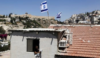 A man is seen from a window as Israeli flags fly on top of a house in Silwan neighborhood of east Jerusalem, August 27, 2015.
