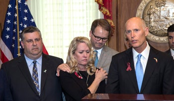 Florida Gov. Rick Scott, right, before he signs the Marjory Stoneman Douglas Public Safety Act in the Governor's office at the Florida Capital in Tallahassee, Fla., March 9, 2018.