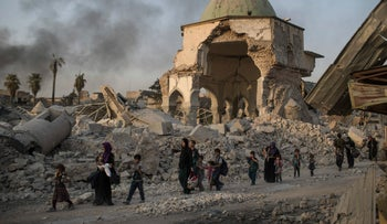 FILE PHOTO: Iraqi civilians fleeing walk past the destroyed al-Nuri mosque as Iraqi forces continue their advance against Islamic State militants in the Old City of Mosul, Iraq, July 4, 2017.