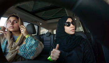 Fatima Salem, right, giggles as Sara Ghouth adjusts her veil, during training sponsored by Ford Motor, in Jiddah, Saudi Arabia, Tuesday, March 6, 2018. A stunning royal decree issued last year by King Salman announcing that women would be allowed to drive in 2018 upended one of the most visible forms of discrimination against women in Saudi Arabia. (AP Photo/Amr Nabil)