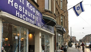 The Israeli flag flies over a a kosher restaurant in Amsterdam on December 7, 2017, where a man  smashed the windows before being detained by police.