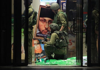 Israeli soldiers confiscate Islamist Hamas movement's flags and posters as they raid the students' union at Bir Zeit University near Ramallah overnight on June 19, 2014