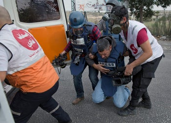 Palestinian paramedics evacuate an injured journalist during clashes with Israeli troops following protests against U.S. President Donald Trump's Jerusalem decision. Ramallah, Dec. 22, 2017