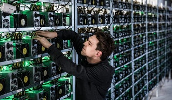 Blockchain mining: Sebastian Kastner of HydroMiner GmbH handles cable connections between cryptocurrency mining rigs, January 19, 2018.