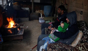 Palestinians warm themselves by a fire inside their house on a rainy day in Al-Shati refugee camp in Gaza City, January 17, 2018.