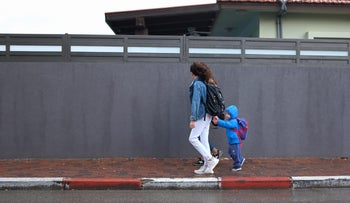 FILE PHOTO: An Israeli mom walks with her children in the rain
