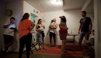 FILE PHOTO: Israelis take cover in shelter as a siren sounds during a rocket attack fired by Palestinian militants from Gaza, in Tel Aviv, Israel, July 12, 2014.
