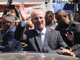 Palestinian Prime Minister Rami Hamdallah is greeted by Hamas' security chief Tawfiq Abu Naim upon his arrival in Gaza City, March 13, 2018.