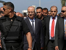 Palestinian Prime Minister Rami Hamdallah, center left, is surrounded by bodyguards as he arrives for the opening ceremony of a sewage plant project in the northern Gaza Strip, March 13, 2018.