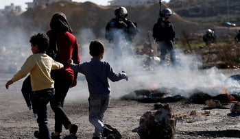 Palestinian children pass by Israeli troops during clashes near Ramallah in the West Bank.