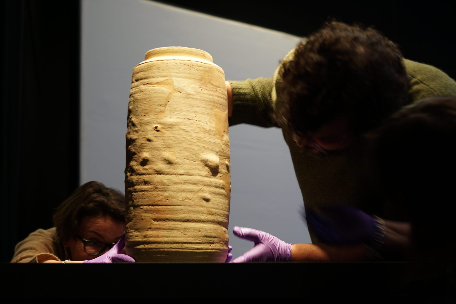 Carefully placing a pottery jar in the Dead Sea Scrolls Exhibition, Denver