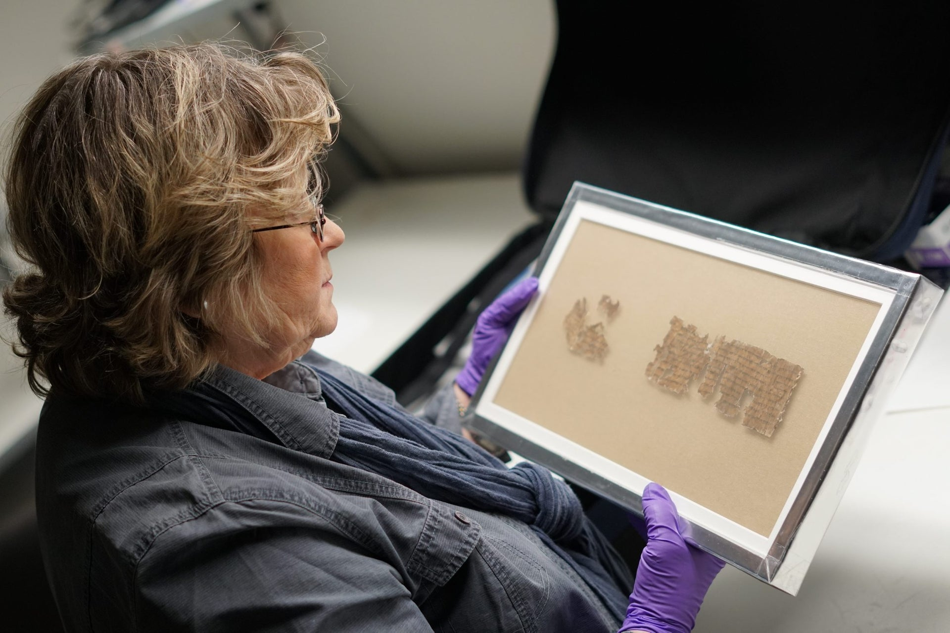 Preserver Tatiana Treiger holding the Tohorot scroll fragment. Photo shows a light-haired woman, whose face cannot be seen (but we can see that she is wearing glasses), holding a framed bit of the Dead Sea Scrolls.