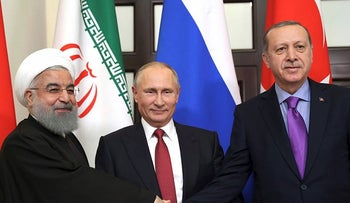 In this Nov. 22, 2017 file photo, Turkey's President Recep Tayyip Erdogan, right, Russia's President Vladimir Putin, center, and Iran's President Hassan Rouhani pose for the media members in Sochi, Russia