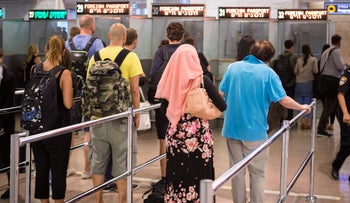 People stand in line to have their passport checked at Tel Aviv's Ben-Gurion Airport.