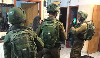 Israeli soldiers raid the home of the Palestinian assailant who killed two soldiers in a West Bank car-ramming attack, March 16, 2018.