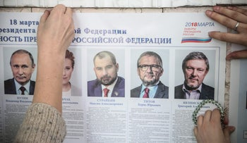 Members of a local election commission install a poster displaying presidential candidates, March 17, 2018, Simferopol, Crimea.