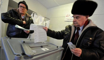 Two men cast their ballots at a polling station in Yelizovo in Russia's Far East region, March 18, 2018.