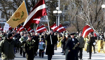 People participate in the annual procession commemorating the Latvian Waffen-SS (Schutzstaffel) unit, also known as the Legionnaires, in Riga, Latvia March 16, 2018