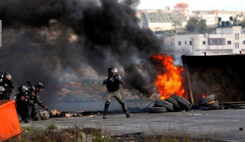 Israeli security forces take aim during clashes with Palestinian following a demonstration in  Ramallah, on March 16, 2018