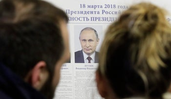 People look at a poster of candidates inside a polling station during presidential elections in St. Petersburg, Russia, March 18, 2018.