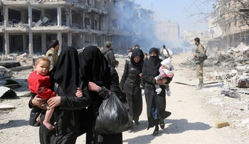 Syrian women and children walk past government soldiers as they evacuate from the town of Jisreen on Saturday. Many women have been abandoned by or separated from their husbands during the war.