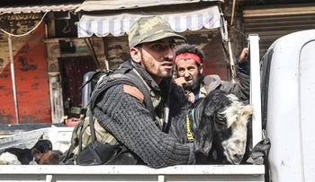 Turkish-backed Syrian Arab fighters ride the back of a pick-up with looted livestock after seizing control of the northwestern Syrian city of Afrin from the Kurdish People's Protection Units (YPG) on March 18, 201