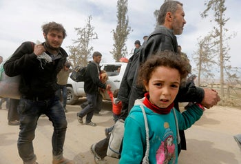 Syrian civilians evacuated from the Eastern Ghouta enclave pass through the regime-controlled corridor east of the enclave town of Hammuriyeh on the outskirts of Damascus. March 18, 2018