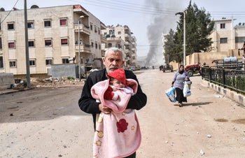 Civilians run cover from explosions in the city of Afrin in northern Syria after Turkish forces and their rebel allies took control of the Kurdish-majority city. March 18, 2018