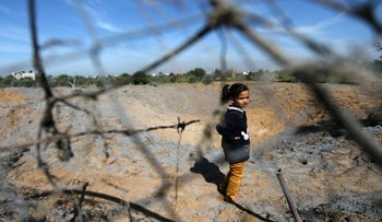 A Palestinian girl stands at the scene of an Israeli air strike, south of Gaza City. March 18, 2018