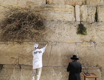 Western Wall Rabbi Shmuel Rabinowitz and a worker clear notes placed in the cracks of the Western Wall to create space for new notes ahead of the Jewish holiday of Passover, in Jerusalem's Old City, March 20, 2018.