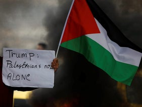 A demonstrator holds a sign and a Palestinian flag during clashes with Israeli troops at a protest against U.S. President Donald Trump's decision to recognize Jerusalem as the capital of Israel. Nablus, December 29, 2017