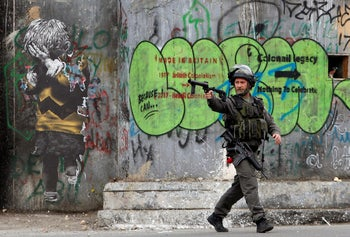 An Israeli border policeman aims his weapon during clashes with Palestinians at a protest against Donald Trump's decision to recognize Jerusalem as the capital of Israel. Bethlehem, December 20, 2017.